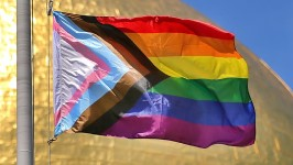Image of the Pride Progress flag, with the brown, black, pink, and blue chevron, flying over a blue sky.