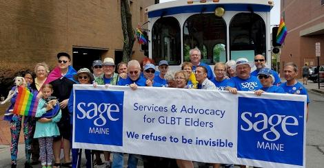 A photo of many SAGE Maine members at a pride parade. They are holding a banner with the SAGE Maine logo.
